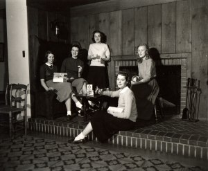 Photograph of five female students sitting by the fireplace in the American Room of Welch Hall at Iowa State University.