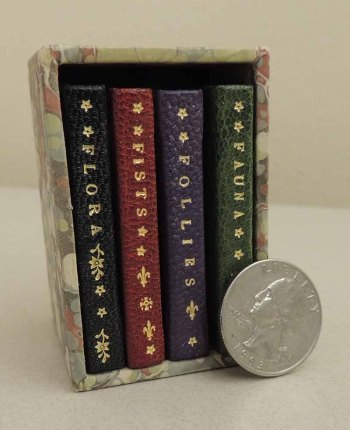 Collection of four miniature books in a slipcase, with a quarter for scale.