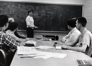 This photograph shows students sitting at a table and the teacher at the chalkboard.