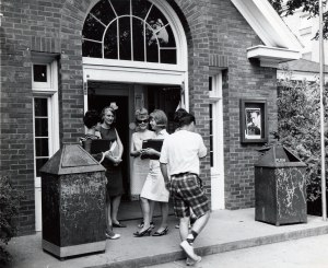 This photograph shows several students standing outside the entrance to the hub talking.