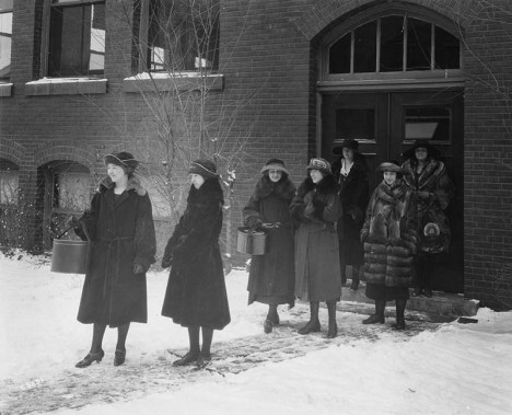 A group of women sets out from a brick building at Iowa State University in the winter of 1915. All are wearing coats and hats, and carying hatboxes. Several of the coats appear to be made of fur (racoon?); others appear to be a heavy wool.