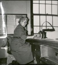 Edna C. Mitchell sitting at desk.