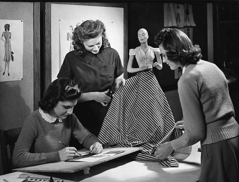 Three women students ca. 1940 work in a Textiles and Clothing classroom decorated by bulletin boards showing current fashions. Two are working with a striped fabric and a small manequin or dress form: one is draping and the other appears to be cutting. The third is working with a pencil on a small drawing board.