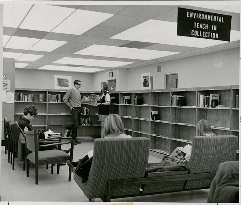 "Two students hold a book entitled ""Man: An Endangered Species?"" amid the low shelves of the Environmental Teach-In Collection, while other students sit in the chairs near the collection."