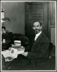 Perry Holden seated at a desk covered in papers and ears of corn.
