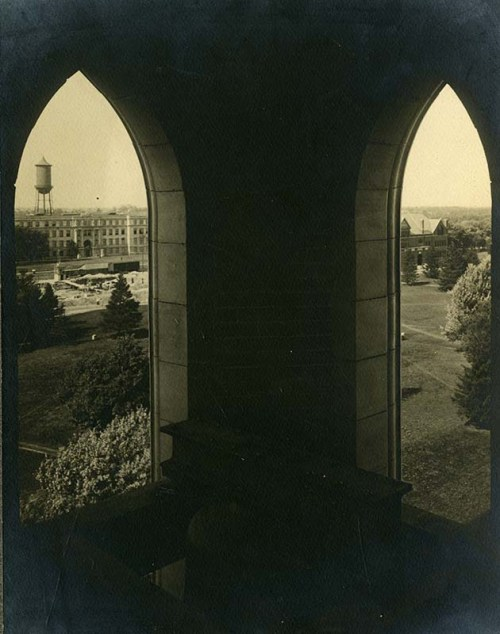 View looking northwest from the bell tower of the Campanile, . Through the left window is visible the erection of Beardshear Hall with Marston Hall and Martson Water Tower in the background. Through the right window Morrill Hall can be seen. A bell can be faintly seen at the bottom.