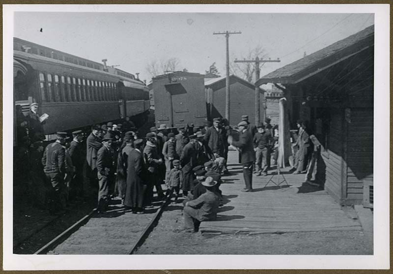 Group of farmers stand on tracks outside a train car, while a man lectures to them from the platform.