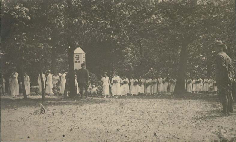 """A row of women dressed in white dresses and carrying flowers processes through the college cemetery past a monument that reads, """"to our 117 dead."""" A row of soldiers is at the right of the picture, and a general stands under a tree in the middle of the image, facing toward the monument."""