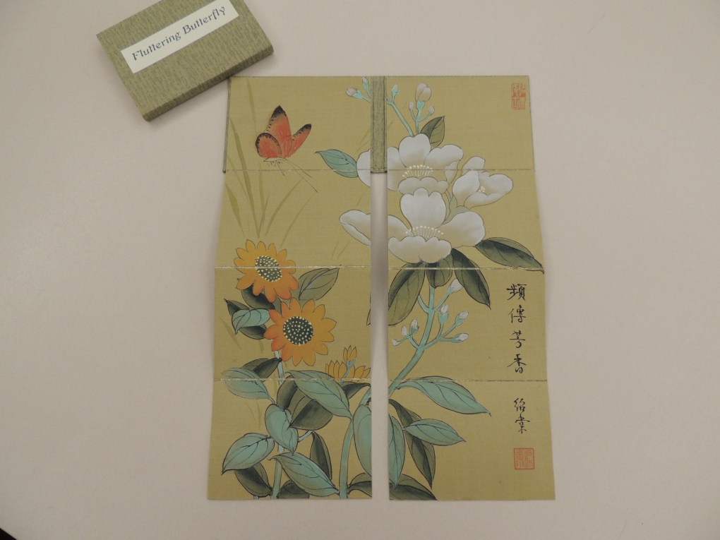 Shows two side-by-side panels of silk unfolded to reveal image of flowers with a butterfly in the upper left corner.