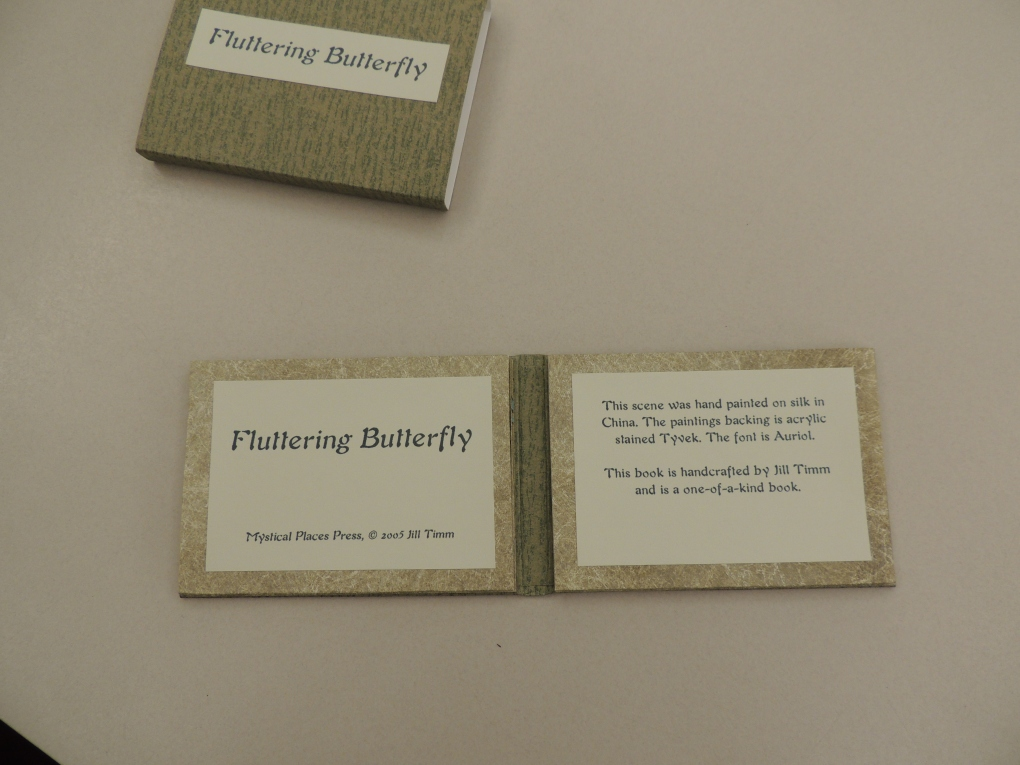 """Shows a slipcover and title page and colophon for Fluttering Butterfly. Colophon reads, """"This scene was hand painted on silk in China. The paintings backing is acrylic stained Tyvek. The font is Auriol. This book is handcrafted by Jill Timm and is a one-of-a-kind book."""""""