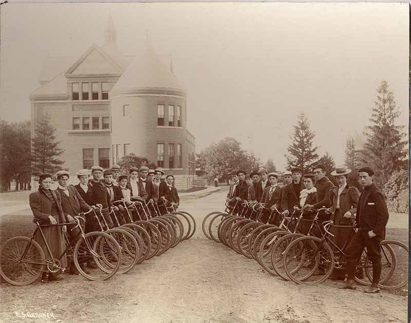 Two rows of men and women standing with their bicycles.