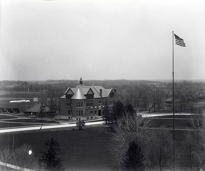 This photograph shows a view of Morrill Hall, possibly as seen from the Campanile. In the foreground is the flagpole and behind Morrill Hall is the Hub and the athletic field.