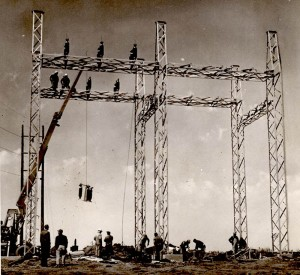 Two men stand on top of the metal scaffolding of an electric substation, while a large piece of equipment is lilfted on a wire by a crane. Ten men work or watch from below.