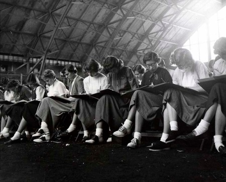 Row of freshman girls wearing blouses and skirts with saddle shoes and loafers, sitting at desks in a large building, taking exams.