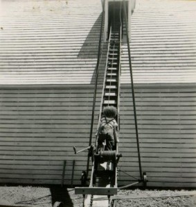 A child climbs up a crop conveyor belt that leads into the corn crib on the Irving Sorenson family farm - an example of what not to do during harvest time, 1953, RS 9/7/F.