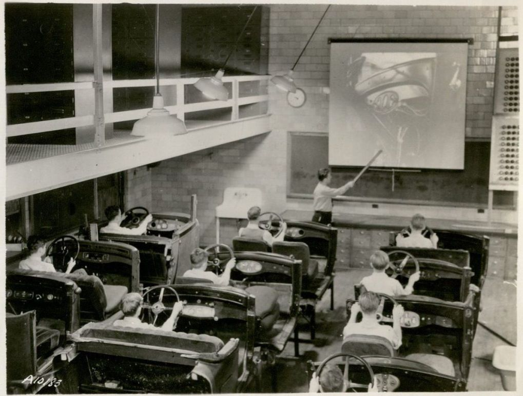 Nine students sit in individual dummy cars (with steering wheels and controls but no wheels) in a large classroom, while a teacher lectures from the front of the classroom pointing to a projected image of a car.