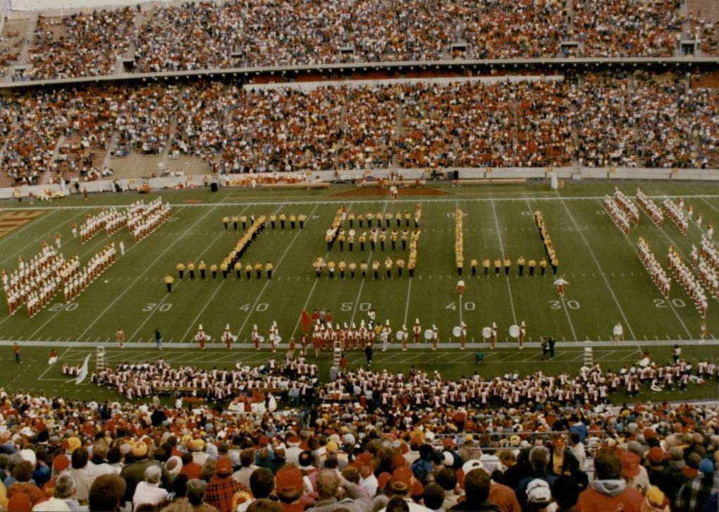 "Iowa State University Alumni Band, where gold and black uniforms, create an ""ISU"" formation on the football field during the half-time show."