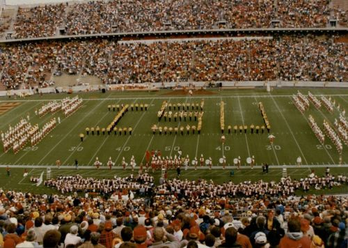 """Iowa State University Alumni Band, where gold and black uniforms, create an """"ISU"""" formation on the football field during the half-time show."""