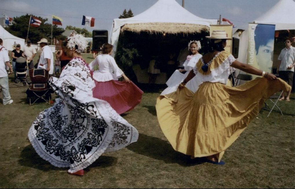 Four women performing folklorico in front of a Panama heritage tent.