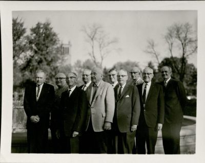Photo shows ten men in suits, members of the ambulance corps, posing outside. In the background is the campanile on the ISU campus.
