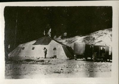 Photo shows a lare tent with a man standing in front with two ambulance trucks parked to the side.