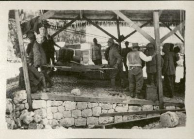 Photo shows two men carrying a stretcher on which another man is laid. Several other men are engaged in various tasks.