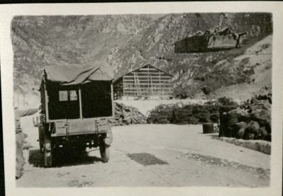 Photo show sthe back of an ambulance open with a stretcher being lowered onto the ground from the air against a background of mountains.