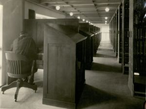 A view of the stacks in the then-new library, with a male student working in a study carrel, April, 1925.
