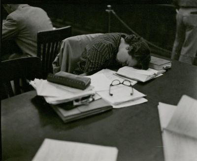 A student looking exhausted and resting in the library, 1957.