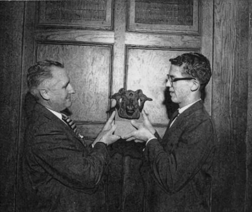 Arloe Paul ('33) passes on the ram's head to Jerry Ladman ('58). (RS 21/7/1, Arloe Paul)