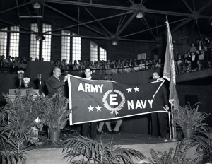 Flag received at the ceremony. Figure holding the flag on the left is Maj. Gen. Leslie R. Groves. Each star represents six months worth of meeting assigned production of war materials. (negative #118186, University Photographs)