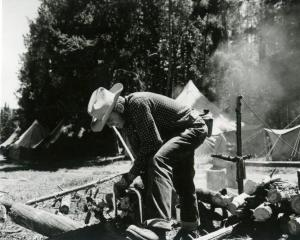 A student preparing firewood at Forestry Summer Camp in Medicine Bow National Forest, Wyoming, 1954. [collection/box]