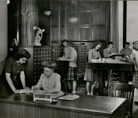 Information desk in Iowa State College library. Ida Robertson, cataloger, helps student look up reference in card file. Kathryn Renfro, cataloger, at information desk looks up some information in a reference book, 1945. University Archives Photograph Collection, box 2046.