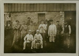 Nine male students and 3 men in period clothing standing or sitting holding rakes, brooms, or milking pails.