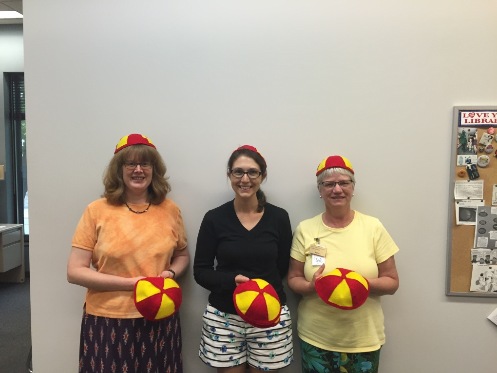 (L-R): Kris Stacy-Bates, Heather Lewin, and Kathy Parsons wearing facsimiles of freshman beanies they made