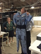 Leo Landis, State Curator, holds up Peggy Whitson's space suit