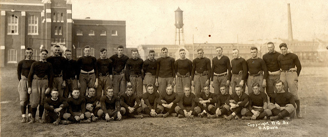 Iowa State varsity football team. In the background are State Gym, Marston Water Tower, and engineering buildings, 1916, taken by D.A. Davis.