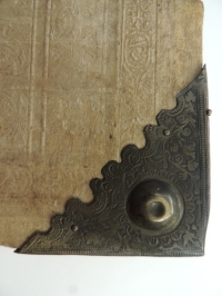 Metal corner on edge of book featuring an upraised knob in center