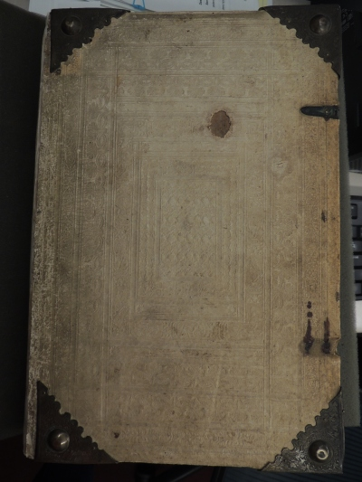 Cover of book in light-colored leather with metal pieces in the corners