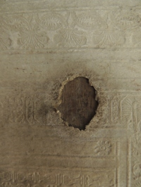 Close up of hole in leather showing wooden board underneath