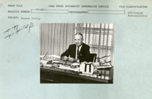 "roof file with photo of Normal Borlaug sitting at desk, his signature on photo, 1977. Filed as ""Off-Campus Personalities"" Negative Number 77-261 with notes ""now copy negs in Spec Coll file"""