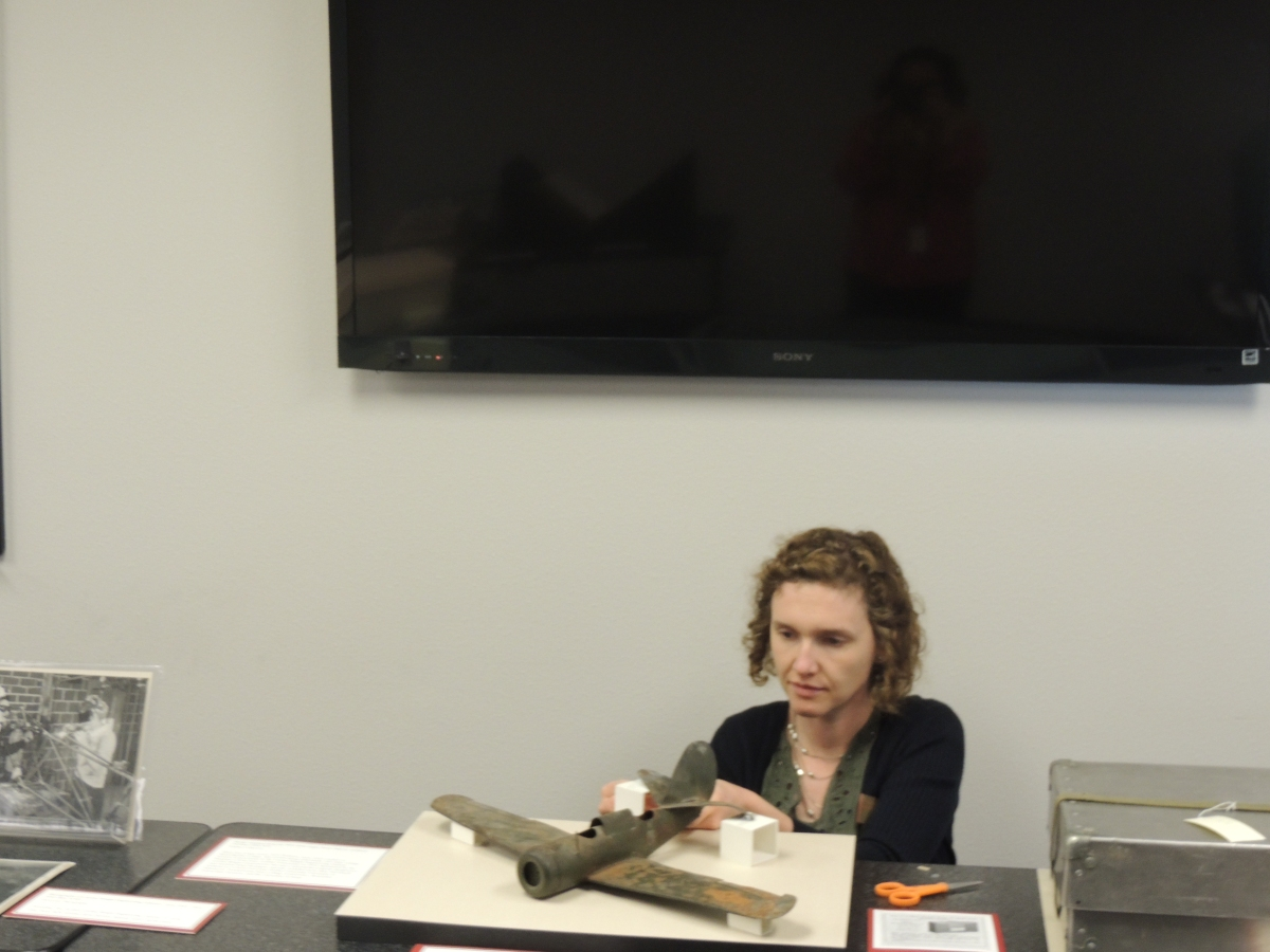 Conservator Sonya Barron getting model plane safely positioned for exhibit