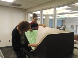 Sonya Barron, Conservator, and Dept. Head Petrina Jackson position elephant folio for exhibit (Photo by Rachel Seale)