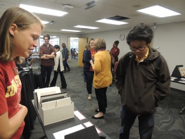 Collections Archivist, Laura Sullivan, talking to student about oldest book in the library and a Civil War diary from Van Zandt Family Papers