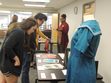 Students looking at table with student publications and Betty (Goodhue) Keeney Papers (unprocessed) including 4-H scrapbook & uniform