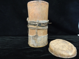 Kenyan Fat Pot, wide cylindrical object with a lid and a handle. Lid is off and handle not visible from this view.