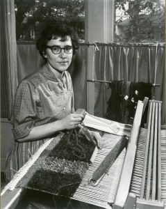 Black-and-white photograph of woman, in her 30s or 40s, short brunette hair and glasses, sitting at a loom.