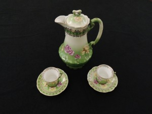Pot and two teacups and saucers, for drinking chocolate. Colors are white embellished with pink and yellow roses.