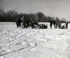 students pulling other students on toboggans, snowy landscape