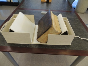 Large books sits in an open box with sides raised at angles to support the book when it is opened.